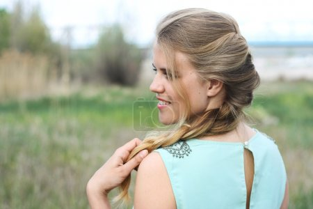 Spring portrait smiling young girl in profile with hair in braid