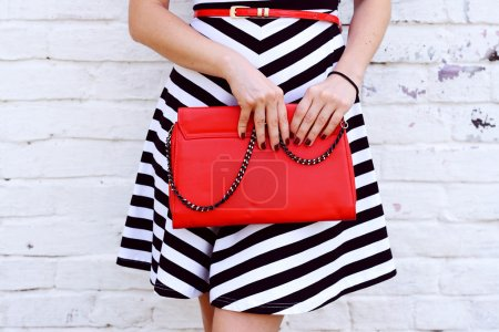 Outdoor Fashionable girl near white street wall .Marine and retro style. striped dress with red handbag clutch