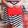 Fashion young woman with red handbag clutch in han...