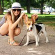 Happy smiling young woman playing with Beagle dog outdoors in the park. summer