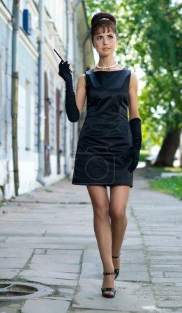 Photo pour Belle fille à l'image d'Audrey Hepburn marchant dans la rue - image libre de droit