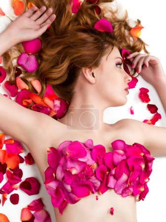 Female waxing armpit in a beauty salon. Ideal smooth clear skin. Beautiful woman lying in rose petals. Depilation. Epilation
