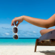 Young girl lying on a beach lounger with glasses i...
