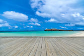Wooden gray pier on perfect beach in sunny day with blue sky