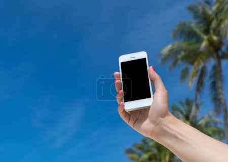 Woman hand showing a blank smart phone on the beach with the sea in the background