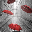 Red umbrellas flying on the street. Conceptual, su...