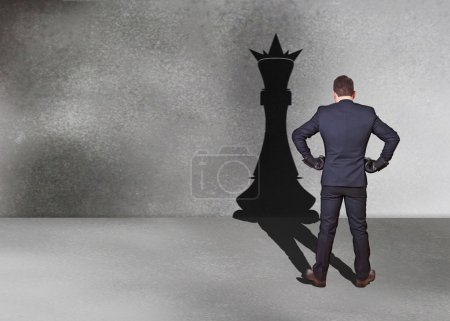 Businessman with chess king shadow
