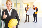 Happy confident business woman holding hardhat giving thumbs up