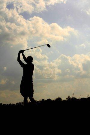 Male Golfer Swings To Hit Golf Ball