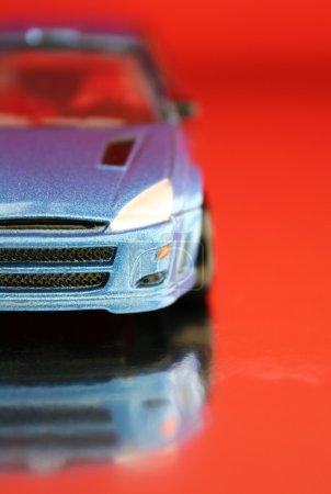 Photo pour Gros plan d'une voiture jouet bleue sur fond rouge avec réflexion. DOF peu profond avec accent sur l'avant de la voiture . - image libre de droit