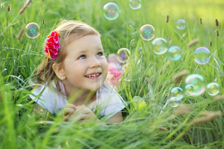 Photo for Sweet, happy, smiling three year old girl laying on a grass in a park playing with bubbles - Royalty Free Image