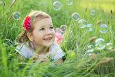 šťastná holčička hraje s bublinami