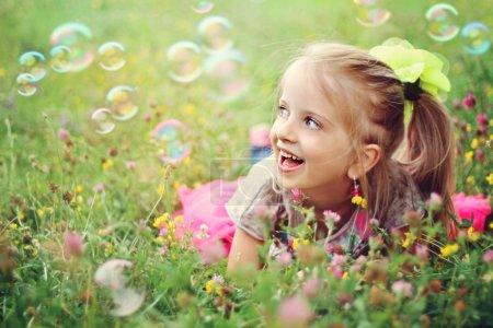 Photo pour Douce, heureuse, souriante fille de six ans allongée sur une herbe dans un parc jouant avec des bulles et riant - image libre de droit
