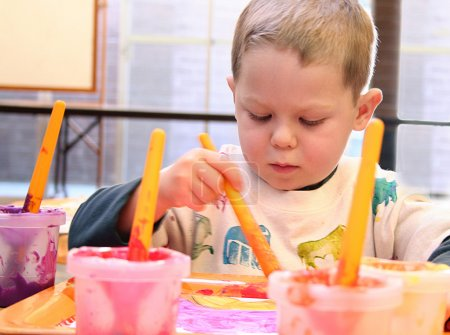 Foto de Enfocado a niño de cuatro años pintando en clase de arte. - Imagen libre de derechos