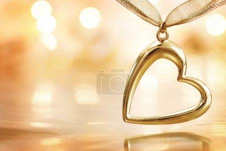 Golden heart on blazing defocused lights background