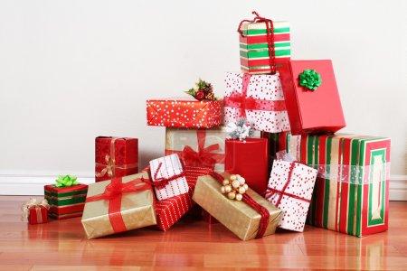 Photo pour Un tas de cadeaux de Noël dans un emballage coloré avec rubans contre le mur sur un plancher de hardoow belle avec fond. - image libre de droit