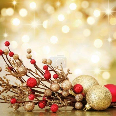 Foto de Bola de Navidad roja y dorada sobre fondo de luces doradas desenfocadas. DOF poco profundo . - Imagen libre de derechos
