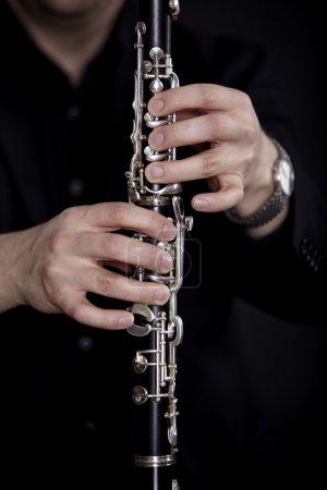 Photo pour Joueur de clarinette en face de fond noir - image libre de droit