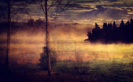 Landschaft mit See und Herbstwald.