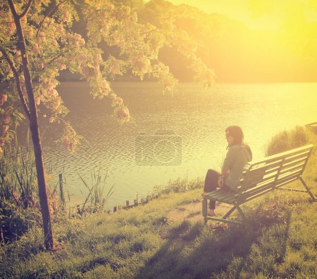 Photo for Woman with lake in front of her while sitting on a park bench - Royalty Free Image