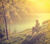 Woman with lake in front of her while sitting on a park bench