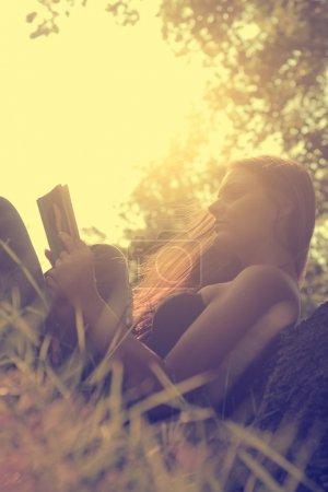 Photo pour Vintage photo de jeune femme lisant un livre dans le parc - image libre de droit