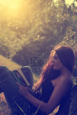 Vintage photo of young woman reading a book in park