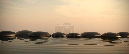 Photo pour Pierres zen dans l'eau avec lever de soleil sur le fond - image libre de droit