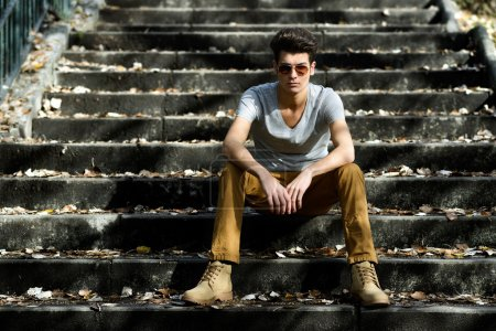 Attractive young handsome man, model of fashion in stairs