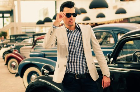 Photo for Portrait of a young handsome man, model of fashion, wearing jacket and shirt with old cars - Royalty Free Image