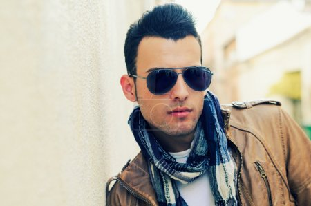 Photo pour Portrait d'un jeune homme séduisant, mannequin de mode, portant des lunettes de soleil teintées en fond urbain - image libre de droit