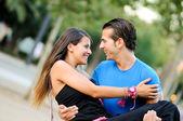 Love couple embracing outdoor in park looking happy