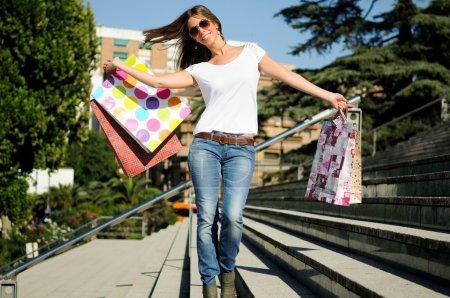 Photo pour Attrayant jeune fille avec des sacs à provisions dans la rue - image libre de droit