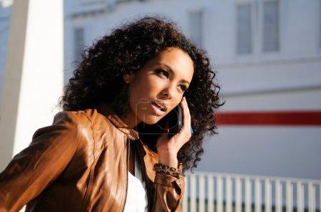 Foto de Retrato de mujer bonita blak fondo urbano hablando por teléfono - Imagen libre de derechos