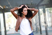 Young black woman, model of fashion in urban background