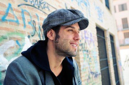Portrait of handsome man in urban background wearing a retro cap
