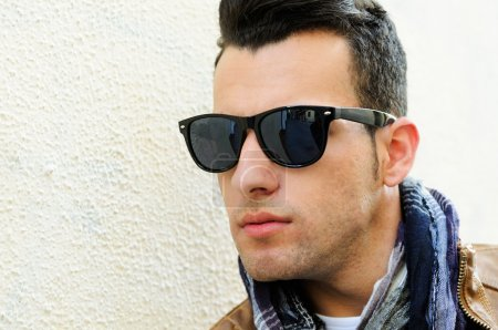 Attractive man wearing tinted sunglasses in urban background