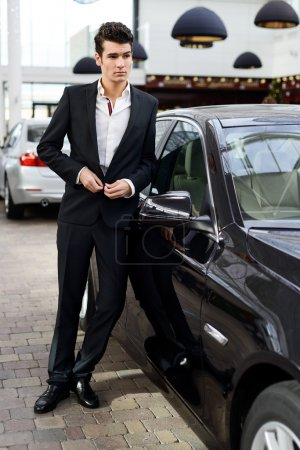 Young handsome man, model of fashion, with luxury cars