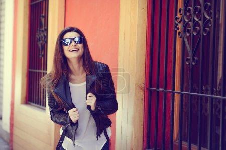 Photo pour Portrait de belle japonaise riant en fond urbain vêtue d'une veste en cuir - image libre de droit