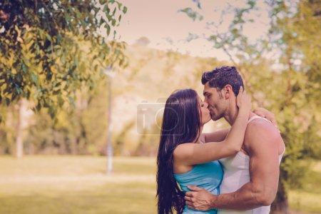 Photo pour Séduisante jeune couple s'embrassant dans un magnifique parc - image libre de droit