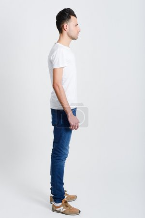 Photo for Portrait of a smart serious young man standing against white background - Royalty Free Image