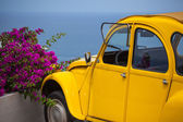 Yellow retro car and summer flowers
