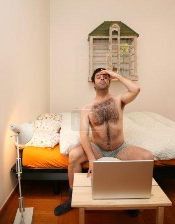 Photo pour Homme dans la chambre avec ordinateur portable - image libre de droit