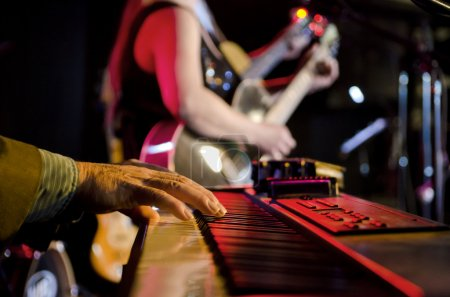 Photo for Selective focus on the hands on the keyboard at a blues festival with guitar players in the background - Royalty Free Image