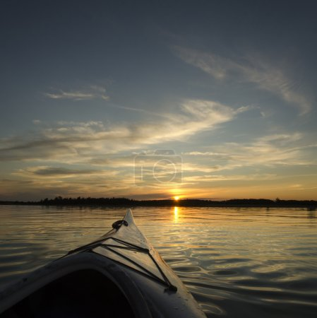 Photo for Kayak on the lake with the treeline and sunset in the background. This is a compsite image using two horizontal images placed together - Royalty Free Image