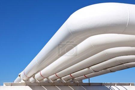 Photo pour Tuyauteries industrielles avec gaz et de pétrole et de l'eau sur un fond de ciel bleu - image libre de droit