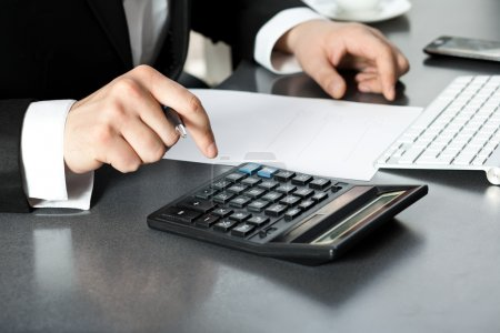 Photo pour Homme d'affaires au bureau assis par ordinateur et trouve la calculatrice - image libre de droit