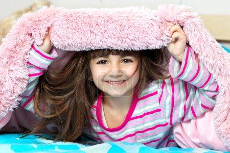 Photo pour Jeune fille souriante sous la couverture rose - image libre de droit