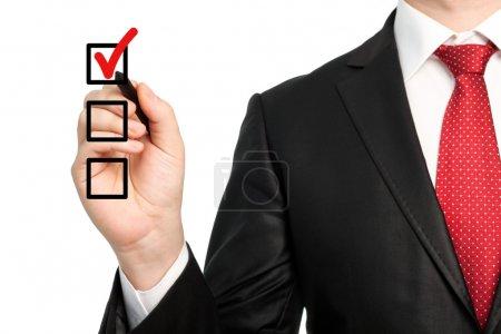Photo pour Homme d'affaires isolé en costume avec une cravate rouge tenant un stylo et écrivant coche rouge ou faire un choix - image libre de droit