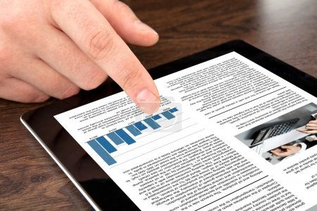 Male hand touching tablet with business news on screen